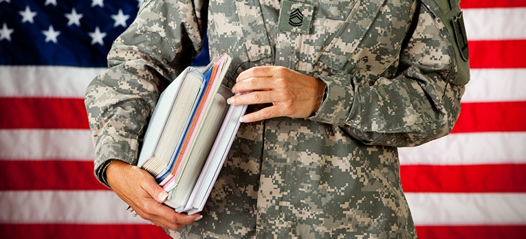 Picture of a person in military fatigues with textbooks in their arms.