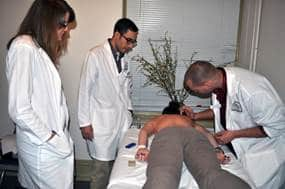 Picture of two student practitioners treating a patient in the student acpuncture clinic with a Clinic Supervisor.
